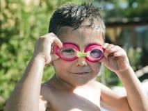 Bambino sveglio con gli occhiali di protezione che ride nello stagno Immagini Stock Libere da Diritti