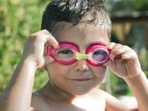 Bambino sveglio con gli occhiali di protezione che ride nello stagno Immagine Stock Libera da Diritti
