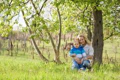 Bambino sveglio con la sua mamma all'aperto in natura. Fotografie Stock Libere da Diritti