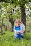 Bambino sveglio con la sua mamma all'aperto in natura. Immagine Stock Libera da Diritti