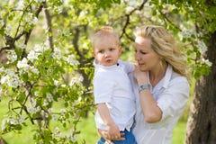 Bambino sveglio con la sua mamma all'aperto in natura. Fotografia Stock