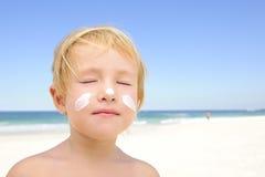 Bambino sveglio con protezione solare alla spiaggia Fotografie Stock Libere da Diritti