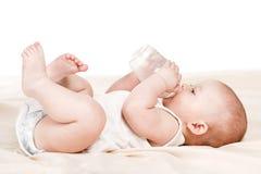 Bambino sveglio con una bottiglia di latte su una coperta beige Fotografia Stock