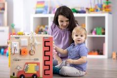 Bambino sveglio del bambino che gioca con il busyboard Giocattoli educativi del ` s dei bambini immagine stock libera da diritti