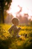 Bambino sveglio del ragazzo che si siede nell'erba Fotografia Stock