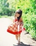 Bambino sveglio della bambina che porta un vestito all'aperto di estate soleggiata Fotografia Stock