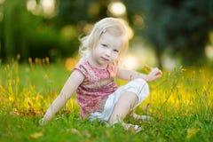 Bambino sveglio della bambina che si siede sull'erba Fotografia Stock Libera da Diritti