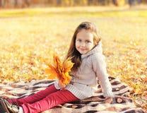 Bambino sveglio della bambina con le foglie di acero gialle in autunno Immagini Stock Libere da Diritti