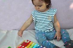 Bambino sveglio della neonata del bambino che gioca con lo xilofono a casa Concetto di istruzione e di creatività stert in antici fotografia stock libera da diritti
