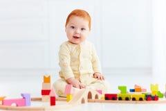 Bambino sveglio dello zenzero che gioca con la strada ferroviaria del giocattolo a casa Fotografia Stock Libera da Diritti