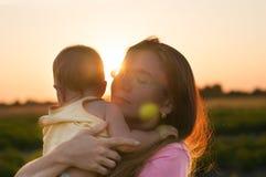 Bambino sveglio nelle armi di una madre felice nei raggi del tramonto Il concetto di buona famiglia immagine stock libera da diritti