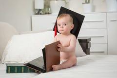 Bambino sveglio in pannolini che indossano le pagine di tornitura del cappuccio di graduazione di grande libro Concetto di istruz Immagini Stock
