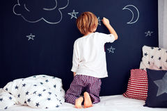 Bambino sveglio in pigiami che dipingono la parete della lavagna nella sua camera da letto fotografia stock libera da diritti