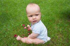 Bambino sveglio sull'erba con i fiori Fotografia Stock