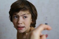 Bambino teenager con timore della siringa di vaccinazione immagine stock