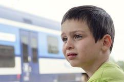 Bambino triste alla fermata del treno immagine stock