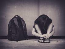 Bambino triste che si siede sul pavimento con il genitore aspettante della borsa di scuola fotografia stock