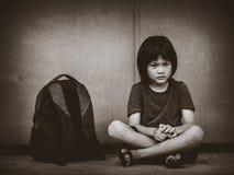Bambino triste che si siede sul pavimento con il genitore aspettante della borsa di scuola fotografia stock libera da diritti
