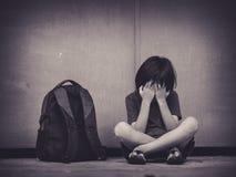 Bambino triste che si siede sul pavimento con il genitore aspettante della borsa di scuola immagini stock