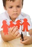 Bambino triste che taglia la sua famiglia di carta della gente Immagine Stock Libera da Diritti