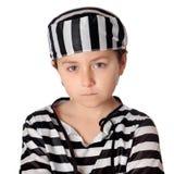 Bambino triste con con il costume a strisce del prigioniero Fotografia Stock Libera da Diritti
