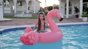 Bambino triste delle vacanze estive ricche dei genitori in palazzo, bambina nel nuoto del costume da bagno sul rosa gonfiabile archivi video