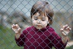 Bambino triste dietro il recinto Fotografia Stock