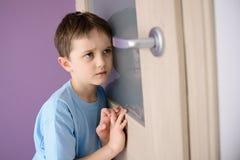 Bambino triste e spaventato che ascolta un genitore che parla attraverso la porta fotografia stock libera da diritti