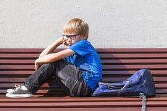 Bambino triste e stanco che si siede da solo sul banco all'aperto Fotografie Stock