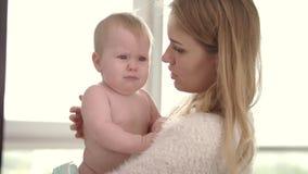 Bambino triste sulle mani della mamma Bambino infantile della giovane tenuta della madre sull'abbraccio stock footage
