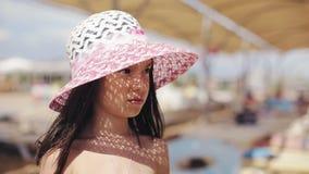 Bambino triste in un cappello su una spiaggia archivi video