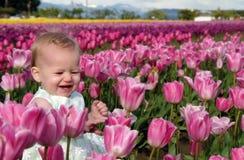 Bambino in tulipani dentellare Fotografia Stock