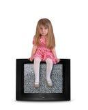 Bambino turbato che si siede sulla televisione in bianco immagini stock