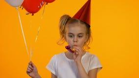 Bambino turbato di compleanno con i palloni facendo uso del ventilatore del partito, celebrante partito da solo video d archivio