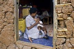 Bambino ugandese di allattamento al seno della madre Immagini Stock