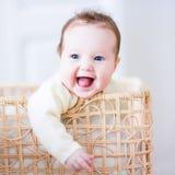 Bambino in un cestino di lavanderia Fotografia Stock