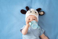 Bambino in un latte alimentare del cappello della mucca Immagine Stock