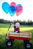 Bambino in un vagone all'esterno Fotografia Stock