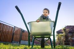 Bambino in una carriola immagini stock