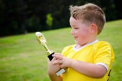 Bambino in uniforme con il suo nuovo trofeo Fotografie Stock