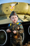 Bambino in uniforme militare sui precedenti del carro armato Fotografia Stock