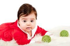 Bambino in vestito da Santa e bagattelle verdi che esaminano macchina fotografica Fotografia Stock