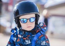 Bambino vestito sicuro per lo sci con il casco, il cablaggio & gli occhiali da sole Fotografia Stock Libera da Diritti