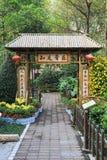 Bamboedeur met Chinees antithetisch couplet en lantaarns, bamboepoort met bestrating, bamboegateway in tuin Stock Foto