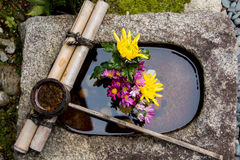 Bamboegietlepel op een steenbassin dat met een bloemstuk in Kyoto Japan wordt gevuld Stock Fotografie
