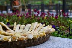 Bamboespruiten die in mand naast bloemen drogen, Chinese keuken, CHINA royalty-vrije stock foto