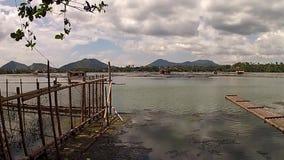 Bamboevlot naast bamboepolen bij het volgende schot van de meerkust stock videobeelden