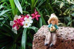 Bambola adorabile che si siede sulla pietra della laterite nel giardino Fotografie Stock