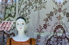 Bambola d'annata contro la vecchia tovaglia del pizzo nella finestra del negozio di Santa Fe con le riflessioni del tetto di matt Immagine Stock