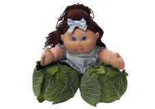 Bambola del giocattolo che si appoggia due cavoli Fotografie Stock Libere da Diritti
